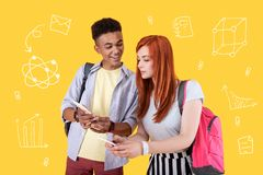 Attentive girl standing with her fellow student and saving his phone number. Sharing phone numbers. Cheerful student smiling while his careful fellow student Royalty Free Stock Photos