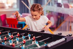 Attentive girl throwing plastic ball on board. Lets start. Concentrated blonde child bowing head while looking at table game royalty free stock images
