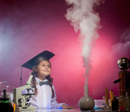 Attentive girl watches evaporation of reagents Royalty Free Stock Photos
