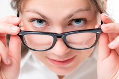 Attentive girl watching glasses having lowered Stock Photography