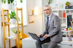 Attentive good-looking tidy man in grey outfit sitting on the edge of the table royalty free stock photography