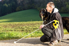 Attentive guide dog. A blind man kneels next to his attentive guide dog Royalty Free Stock Photos
