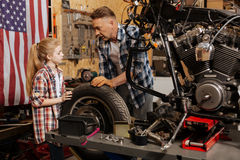 Attentive interested girl helping her dad changing a tire Royalty Free Stock Images