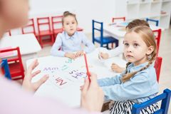 English for kids. Attentive lementary schoolgirl listening to explanation of teacher at lesson of english language stock image