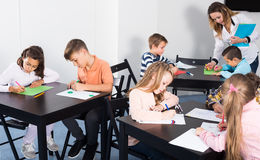 Attentive little children with teacher drawing in classroom. On the lesson Stock Image