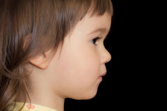Attentive little girl. Little girl attentively looks forward. Profile on black background Royalty Free Stock Image