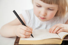 Attentive little girl writing letters Stock Photo