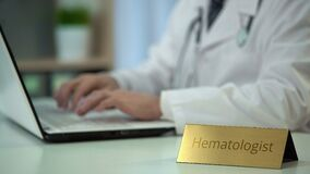 Attentive male hematologist typing medical report on laptop, working in office. Stock footage stock video