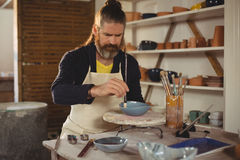 Attentive male potter painting on bowl. In pottery workshop Royalty Free Stock Image