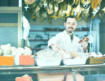Attentive male shop assistant demonstrating sorts of meat in sho Royalty Free Stock Image