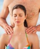 Attentive man applying sun cream on his girlfriend Stock Photos