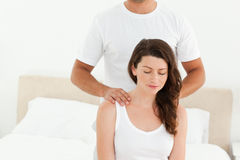 Attentive man doing a back massage to his wife Royalty Free Stock Image