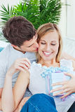 Attentive man giving his girlfriend a present Stock Photography