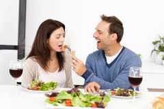 Attentive man giving a tomato to his girlfriend Stock Photography