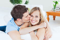 Attentive man kissing his girlfriend. Lying in the living-room Stock Image
