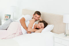 Attentive man looking at his girlfriend sleeping Royalty Free Stock Images