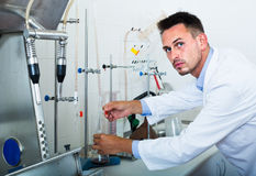 Attentive man making tests in wine manufactory laboratory Royalty Free Stock Photo