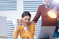 Attentive man putting a hand on a shoulder of his tired colleague. Kind man. Tired young women drinking tea and looking upset while her attentive supporting Royalty Free Stock Photos