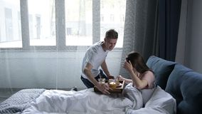 Attentive man serving breakfast to woman in bed stock footage