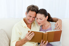 Attentive man and woman looking at a photo album. On the sofa in the living room Royalty Free Stock Photography