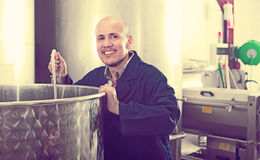 Attentive mature man working in wine secondary fermentation sect Royalty Free Stock Photo