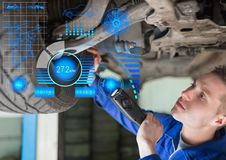 Attentive mechanic repairing hydraulic car. With digitally generated interface stock photo