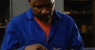 Metalsmith using caliper in workshop 4k. Attentive metalsmith using caliper in workshop 4k stock video footage