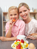 Attentive mother eating fruit with her daughter Stock Images