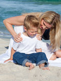 Attentive mother with her son sitting on the sand Stock Photos
