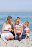 Attentive mother holding sunscreen at the beach Stock Photography