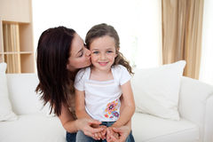 Attentive mother kissing her little girl Stock Image