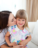 Attentive mother kissing her little girl Royalty Free Stock Image
