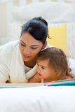 Attentive mother reading with her daughter Royalty Free Stock Photos