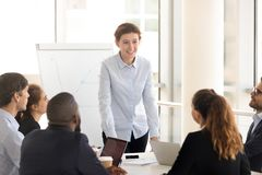 Diverse businesspeople sitting at seminar listen speech of coach woman. Attentive multinational people brainstorming sitting around desk in briefing at boardroom stock photos