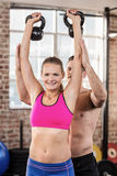Attentive muscular trainer show how to lift kettlebells. In crossfit gym Stock Photo