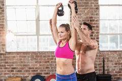 Attentive muscular trainer show how to lift kettlebells. In crossfit gym Royalty Free Stock Image
