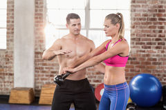 Attentive muscular trainer show how to lift kettlebells. In crossfit gym Stock Images