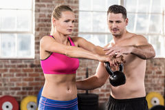 Attentive muscular trainer show how to lift kettlebells. In crossfit gym Royalty Free Stock Photography