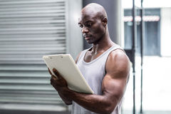 Attentive muscular trainer writing on clipboard Royalty Free Stock Photo