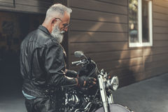 Attentive old man getting ready for trip Stock Photo
