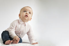 Attentive open-mouthed toddler sitting on the blanket and looking up. Copy space. Postcard Royalty Free Stock Images
