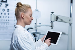 Attentive optometrist using digital tablet Stock Photography