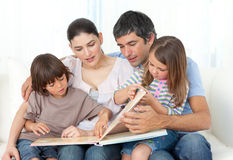 Attentive parents reading with their children Stock Photo