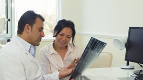 Attentive patient listens to doctor`s advice. The doctor holds the X-Ray of the patient. He tells her what X-Ray shows. The patient listens to him attentively Stock Photos