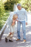 Attentive pensioner helping senior wife outdoors. Full of care . Helpful retired peaceful men caring about his aged wife and helping her to make steps while Royalty Free Stock Images