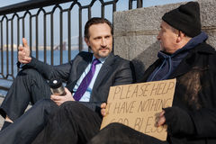 Attentive pensioner listening to his interlocutor. Use gesticulation. Confident bearded men holding thermos in left hand wearing costume, speaking with homeless Stock Photo