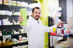 Attentive pharmacist suggesting useful drug. In pharmacy royalty free stock image