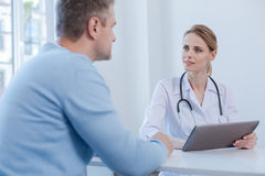Attentive physician listen to patient complaint in the medical cabinet Royalty Free Stock Photo