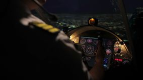 Attentive pilot steering aircraft professionally, night flight above megalopolis stock footage