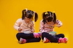 Attentive pretty little sisters sitting on bare floor royalty free stock photo